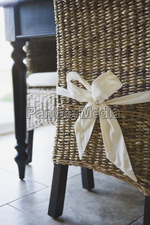 bow tied around wicker dining chair