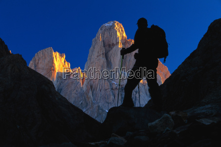 hiker silhouetted against monte fitz roy