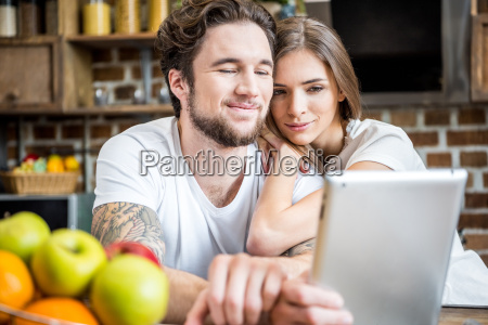 couple using digital tablet at kitchen